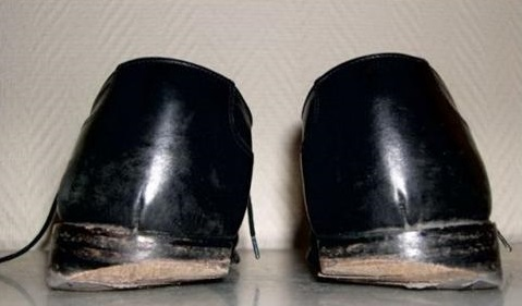 Chaussures avec talons usés vers intérieur